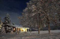 Ισχυρή χιονόπτωση στα δέντρα και σπίτι στη νύχτα Χριστουγέννων Στοκ φωτογραφία με δικαίωμα ελεύθερης χρήσης