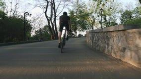 Ισχυροί επαγγελματικοί γύροι ποδηλατών ανηφορικοί από τη σέλα Ισχυροί αθλητικοί μυ'ες ποδιών που το ποδήλατο απόθεμα βίντεο