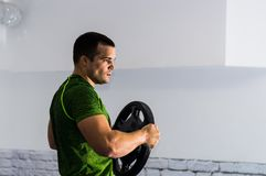 ισχυρός άνδρας που κάνει τις ασκήσεις με το βάρος Στοκ Εικόνες