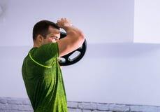 ισχυρός άνδρας που κάνει τις ασκήσεις με το βάρος Στοκ εικόνα με δικαίωμα ελεύθερης χρήσης