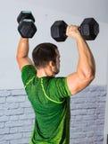 ισχυρός άνδρας που κάνει τις ασκήσεις ώμων στη γυμναστική Στοκ Εικόνα