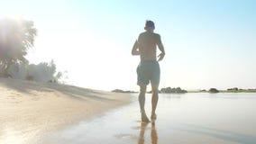 Ισχυρός αθλητής αναμμένος από τα τρεξίματα ήλιων κατά μήκος της ωκεάνιας ακτής αργής απόθεμα βίντεο