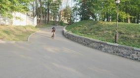 Ισχυρός αθλητικός ποδηλάτης που τρέχει γρήγορα ανηφορικά από τη σέλα Ανερχόμενος λόφος αναβατών ποδηλάτων που φορά μαύρο sportswe απόθεμα βίντεο