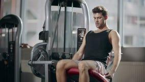 Ισχυρός αθλητικός τύπος που κάνει την άσκηση ποδιών στον αθλητικό προσομοιωτή στη λέσχη ικανότητας απόθεμα βίντεο