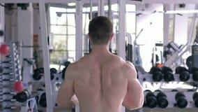 Ισχυρός αθλητικός τύπος που κάνει το μυ που στηρίζεται workout στον προσομοιωτή έλξης για τα χέρια λειτουργώντας στο σώμα στην αθ φιλμ μικρού μήκους