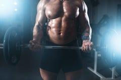 Ισχυρός αθλητής που ανυψώνει το barbell στην αθλητική γυμναστική Στοκ Εικόνες