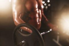Ισχυρός αθλητής που ανυψώνει το barbell στην αθλητική γυμναστική Στοκ Φωτογραφίες
