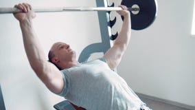Ισχυρός αθλητικός τύπος που κάνει τις μπούκλες δικέφαλων μυών με το barbell φιλμ μικρού μήκους