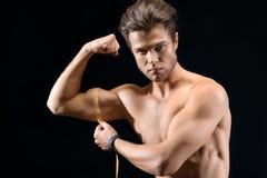 Ισχυρός αθλητικός τύπος που μετρά το bicep του στοκ φωτογραφία με δικαίωμα ελεύθερης χρήσης