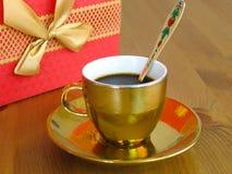 Ισχυρός αρωματικός καφές σε ένα επιχρυσωμένο φλυτζάνι με ένα χρυσό κουτάλι στοκ εικόνες