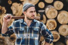 Ισχυρός γενειοφόρος υλοτόμος που φορά το τσεκούρι λαβής πουκάμισων καρό υπό εξέταση στο υπόβαθρο του πριονιστηρίου στοκ φωτογραφίες