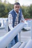 Ισχυρός εργάτης οικοδομών που κυλά το συγκεκριμένο σωλήνα Στοκ Φωτογραφίες