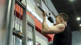 Ισχυρός λεπτός νεαρός άνδρας επαγγελματικό Bodybuilder που δεσμεύεται με το βραχίονα και το ραχιαίο μυ απόθεμα βίντεο