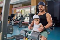 Ισχυρός μπαμπάς και λίγος γιος που κάνουν τις ασκήσεις όπλων που κάθονται στο μεταλλικό προσομοιωτή στοκ εικόνες