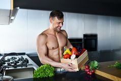 ισχυρός μυϊκός αθλητής που στέκεται στο σύνολο κιβωτίων κουζινών των φρέσκων λαχανικών παντοπωλείων στα χέρια που φαίνονται χαμόγ Στοκ Εικόνα