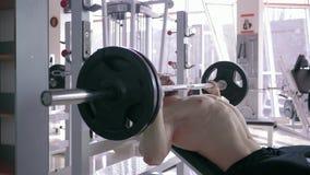 Ισχυρός μυϊκός Τύπος αθλητικών αρσενικός κάνοντας πάγκων με το barbell ενώ δύναμη που επιλύει στη γυμναστική απόθεμα βίντεο