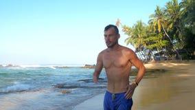 Ισχυρός μυϊκός gymnast με τα κίτρινα τρεξίματα wristwatch φιλμ μικρού μήκους