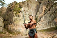 Ισχυρός νέος πολεμιστής με ένα ξίφος Στοκ Εικόνες