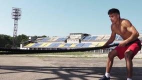 Ισχυρός νεαρός άνδρας που κάνει τις ασκήσεις με ένα σχοινί μάχης υπαίθριο στην ηλιόλουστη ημέρα απόθεμα βίντεο
