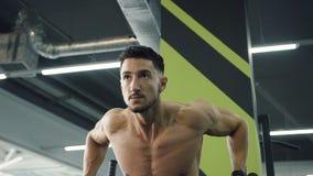 Ισχυρός νεαρός άνδρας που κάνει το τράβηγμα-UPS στους παράλληλους φραγμούς στη γυμναστική απόθεμα βίντεο