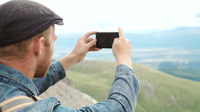 Ισχυρός οδοιπόρος ατόμων που παίρνει τη φωτογραφία με το έξυπνο τηλέφωνο στην αιχμή βουνών Θαυμάσια χαραυγή απόθεμα βίντεο