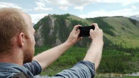 Ισχυρός οδοιπόρος ατόμων που παίρνει τη φωτογραφία με το έξυπνο τηλέφωνο στην αιχμή βουνών Θαυμάσια χαραυγή φιλμ μικρού μήκους