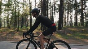 Ισχυρός ποδηλάτης που οδηγά ένα ποδήλατο στο πάρκο Ο ήλιος λάμπει μέσω των δέντρων Η πλευρά ακολουθεί τον πυροβολισμό Έννοια ανακ απόθεμα βίντεο