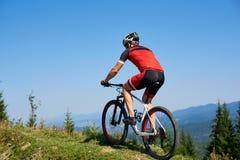 Ισχυρός ποδηλάτης τουριστών ατόμων στο κράνος, τα γυαλιά ηλίου και το πλήρες οδηγώντας ποδήλατο εξοπλισμού στο χλοώδη λόφο στοκ εικόνα με δικαίωμα ελεύθερης χρήσης