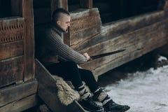 Ισχυρός πολεμιστής Βίκινγκ που ακονίζει το ξίφος του καθμένος κοντά Στοκ Εικόνες