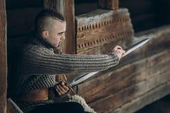 Ισχυρός πολεμιστής Βίκινγκ που ακονίζει το ξίφος του καθμένος κοντά Στοκ εικόνα με δικαίωμα ελεύθερης χρήσης
