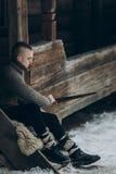 Ισχυρός πολεμιστής Βίκινγκ που ακονίζει το ξίφος του καθμένος κοντά Στοκ Εικόνα