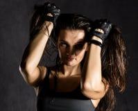 Ισχυρός προκλητικός θηλυκός μαχητής μπόξερ ή mma που φορά τα μαύρα γάντια σε ένα σκοτεινό υπόβαθρο Στοκ Εικόνα