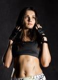 Ισχυρός προκλητικός θηλυκός μαχητής μπόξερ ή mma που φορά τα μαύρα γάντια σε ένα σκοτεινό υπόβαθρο Στοκ Εικόνες