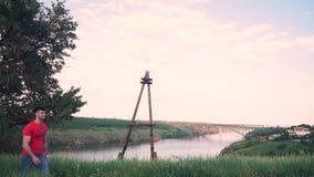 Ισχυρός τύπος που περπατά, ένα όμορφο πράσινο δέντρο, χλόη, στα πλαίσια του ποταμού Dnieper, γέφυρα, κατά μήκος της πορείας απόθεμα βίντεο