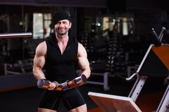Ισχυρός υγιής ενήλικος σχισμένος άνδρας με τους μεγάλους μυς που εκπαιδεύει με το δ Στοκ Φωτογραφία