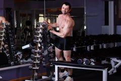 Ισχυρός υγιής ενήλικος σχισμένος άνδρας με τους μεγάλους μυς που επιλέγει dumbbe στοκ φωτογραφία με δικαίωμα ελεύθερης χρήσης