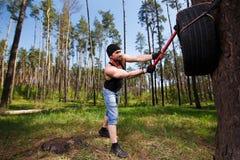 Ισχυρός υγιής ενήλικος σχισμένος άνδρας με τους μεγάλους μυς που χτυπούν το αυτοκίνητο tyr στοκ εικόνα με δικαίωμα ελεύθερης χρήσης