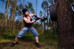 Ισχυρός υγιής ενήλικος σχισμένος άνδρας με τους μεγάλους μυς που χτυπούν το αυτοκίνητο tyr στοκ εικόνα