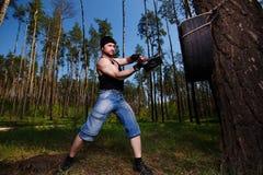 Ισχυρός υγιής ενήλικος σχισμένος άνδρας με τους μεγάλους μυς που χτυπούν το αυτοκίνητο tyr στοκ φωτογραφίες
