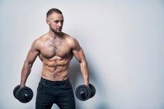 Ισχυρός όμορφος αθλητής που στέκεται με τους αλτήρες στοκ φωτογραφία