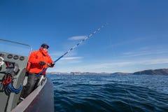 Ισχυρό άτομο με μια ράβδο αλιείας στα χέρια του βάρκα θάλασσας fisherma Στοκ Εικόνες