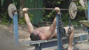 Ισχυρό άτομο που αυξάνει το barbell που βρίσκεται στον πάγκο στο πάρκο Άσκηση για τους δικέφαλους μυς Κράτηση του σώματος στη μορ απόθεμα βίντεο