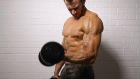 Ισχυρό άτομο που κάνει την άσκηση με τους αλτήρες απόθεμα βίντεο