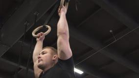 Ισχυρό άτομο που κάνει την άσκηση μυών UPS δαχτυλιδιών στη διαγώνια κατάλληλη γυμναστική απόθεμα βίντεο