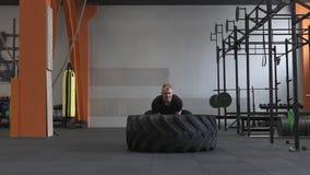 Ισχυρό άτομο που κάνει τη μεγάλη άσκηση κτυπημάτων ροδών στη διαγώνια κατάλληλη γυμναστική φιλμ μικρού μήκους