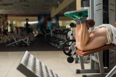 Ισχυρό άτομο που κάνει τον αθλητισμό στη γυμναστική στοκ εικόνα