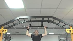 Ισχυρό άτομο που κάνει το τράβηγμα UPS σε μια γυμναστική φιλμ μικρού μήκους