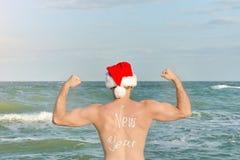 Ισχυρό άτομο στα καπέλα Santa με το νέο έτος επιγραφής στην πίσω στάση στην παραλία υποστηρίξτε την όψη Στοκ Εικόνα