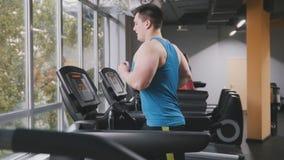 Ισχυρό άτομο στη γυμναστική - bodybuilder τρέχοντας στην τρέχοντας διαδρομή στη γυμναστική Στοκ εικόνες με δικαίωμα ελεύθερης χρήσης