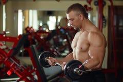 Ισχυρό άτομο - bodybuilder με τους αλτήρες σε μια γυμναστική, που ασκεί το πνεύμα Στοκ Φωτογραφία